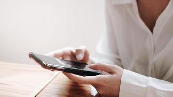 ung asiatisk kvinna som arbetar med smart telefon