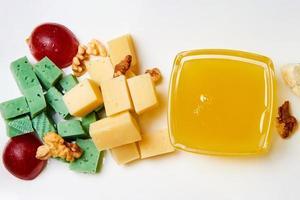 skivad ost med nötter, druvor och honung foto