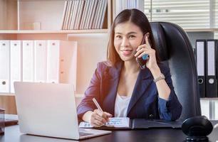 ung asiatisk kvinna som använder smarttelefonen på jobbet foto