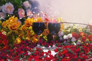 rött vin i klart glas med blommig dekor foto