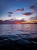 cumulusmoln ovanför havet under solnedgången foto
