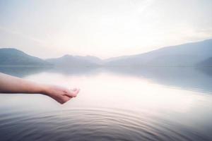 hand skopa vatten från sjön foto