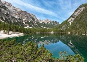 träd, berg och molnig himmel återspeglas i sjön foto