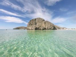 stor klippa i havet med molnig blå himmel