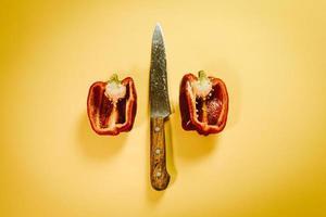 kniv mellan två halvor röd paprika foto