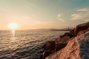 stenig kust vid vatten med låg sol på himlen foto