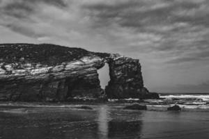 stor stenig klippa och molnig himmel på stranden i monokrom foto