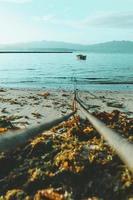 rep som leder till båt i vatten foto
