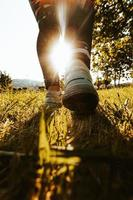 person som går i solen med gräs