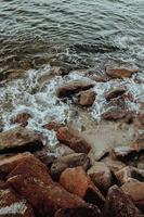 vatten kraschar mot stenar och sand foto