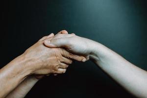 två gamla händer som håller ung hand foto