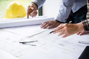 konstruktionsarkitekter diskuterar en plan foto