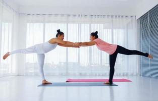 två kvinnor som utövar yoga foto