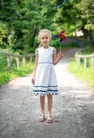 liten flicka med färgglad pinwheel i parken. foto
