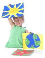 glad tjej som håller målningar med fingerfärger på händerna foto