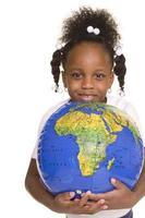 liten flicka kramar världen foto