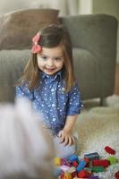 söt liten flicka som leker hemma foto