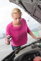 kvinna inspekterar trasiga bilmotorer. foto