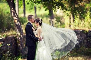 bruden och brudgummen i naturen med utvecklande slöja foto