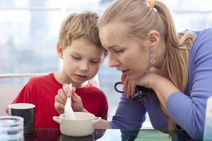 mamma och son äter frukost foto