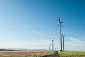 hållbara vindkraftsgeneratorer mot blå himmel; förnybar e foto