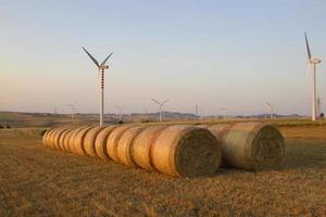 vindkraftverk och höbalar i ett fält foto