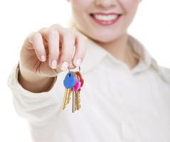kvinna fastighetsmäklare håller inställda nycklar till nytt hus foto