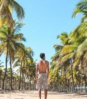 man står bland palmträd på stranden