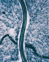 Flygbild uppifrån och ner på en väg mitt i snön foto