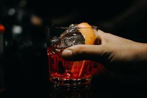 hand som håller cocktail i glas