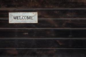 välkomsttecken på träbakgrund foto