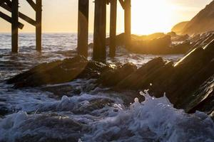 vågor på stranden under gyllene timmen foto