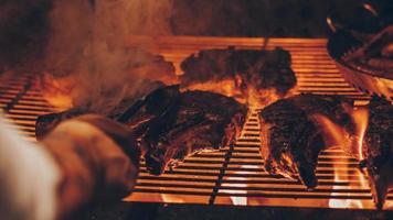 person som grillar kött foto