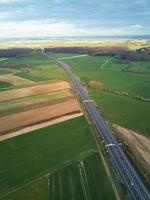 Flygfoto över en motorväg mellan fält med grönt gräs