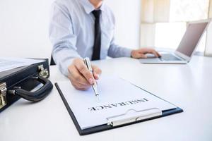 affärsman underteckna en bilförsäkring foto
