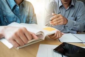 två klasskamrater som lär sig arbetsböcker foto