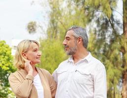 äldre par promenerar lyckligt i parken