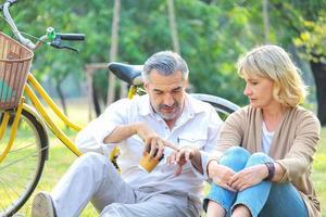 äldre par som sitter på gräsmattan i en park foto