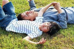 far och son som ligger på gräset foto