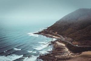 berg bredvid väg och hav foto