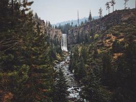 vattenfall mellan träd och kullar foto