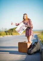 porträtt av härlig ung hippiflicka som liftar på en väg