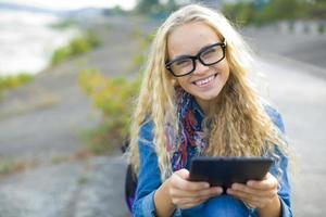 student med en surfplatta utomhus på sommaren foto