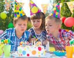barn på födelsedagsfest som blåser ljus på kakan foto