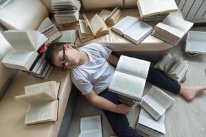trött pojke som sover omgiven av böcker i rummet foto