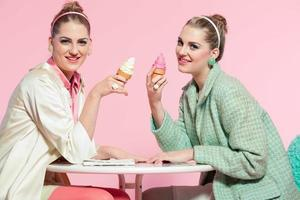 två flickor blont hår femtiotalet mode stil äter glass. foto