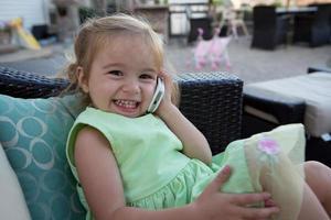 söt liten flicka i telefon foto
