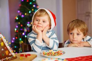 två små syskonpojkar som är glada över en självgjord pepparkakakaka foto