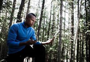 stilig ung man att hitta sin väg i skogen foto