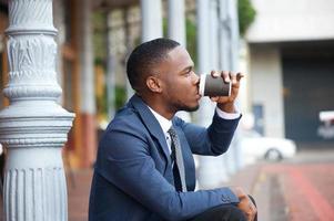 ung affärsman kopplar av och dricker kaffe i staden foto
